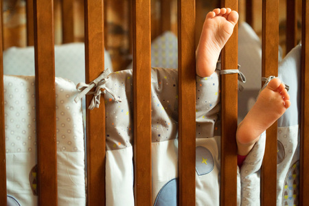 Childs feet stick out of crib