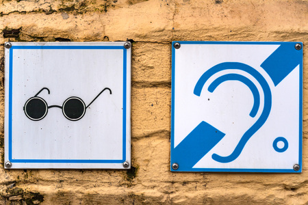 Visual and hearing disability signs on wall