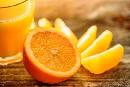 Oranges and orange juice on a wooden background