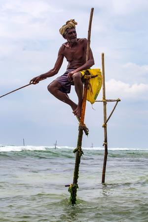 WELIGAMA, SRI LANKA - CIRCA DECEMBER 2013: Stilt fisherman