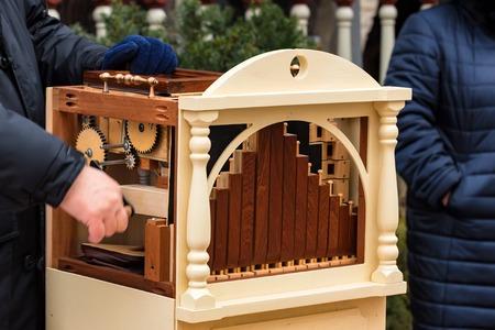 Male hands on barrel organ in street Stock fotó