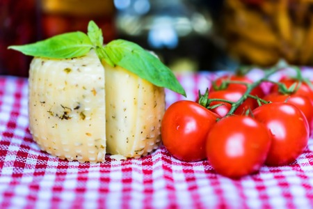Rustic cheese with herbs and tomatoes Stock Photo