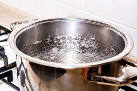 Boiling water for soup in modern saucepan