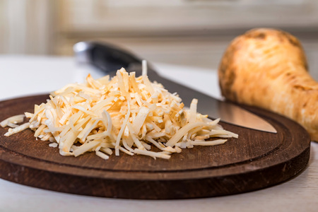 Chopped parsnip on wooden board close