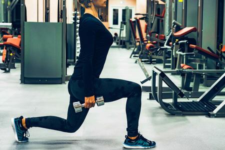 Junge Frau macht Hantel Ausfallschritte im Fitnessstudio