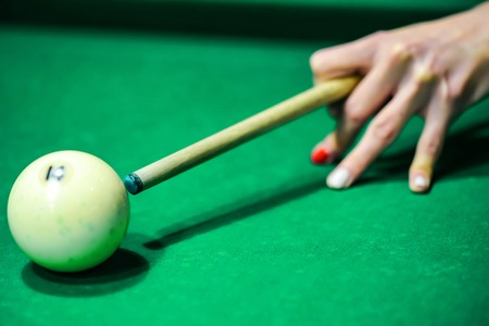 Womans hand with cue playing pool