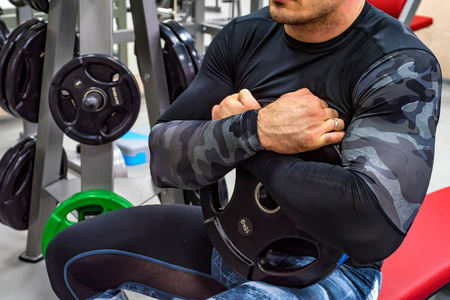 Bodybuilder holds weight plate close Stock Photo