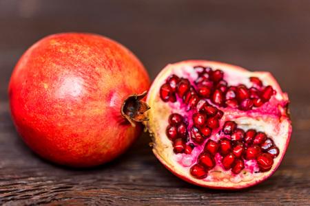 Ripe pomegranate fruits on wooden background Stock Photo