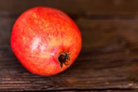 Single ripe pomegranate fruit on wooden background