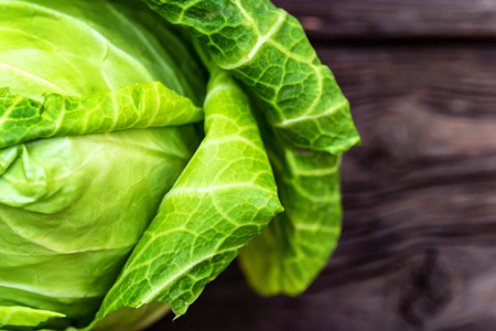 Green fresh cabbage head on wooden surface Stock Photo