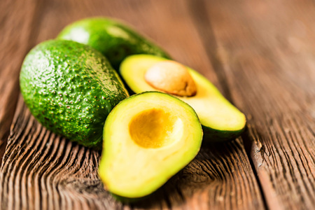 Avocados cut and whole on a wooden background