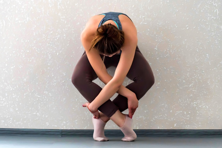 Young woman stands in yoga asana next to wall Stock Photo