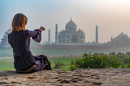 Beautiful girl points to Taj Mahal. Travel concept Stock Photo