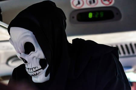 Person in skeleton mask and black hood