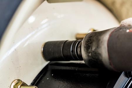 Mechanic assembles wheel using pneumatic screw gun