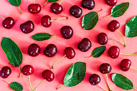 Sweet ripe cherries and leaves on pink background Stock Photo