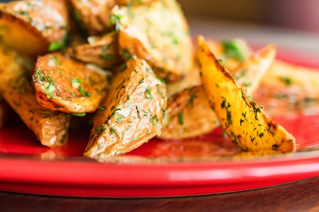 Baked potato wedges with dill and spices close