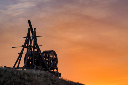 Old wooden catapult against sunset sky background