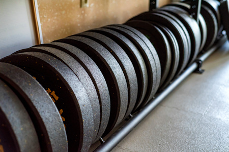 Fitness barbell weight plates in modern gym close
