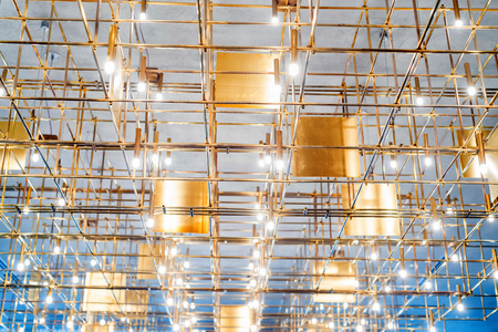 Modern metal lighting construction on the ceiling that looks like bamboo