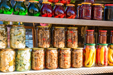 Preserved autumn vegetables and jam in jars Stock Photo