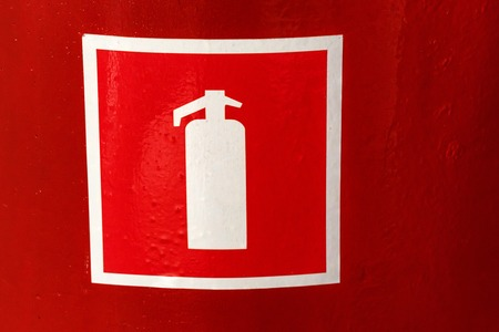 Fire extinguisher symbol on red wall close
