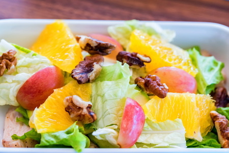 Delicious salad of apple, orange and walnut in bowl