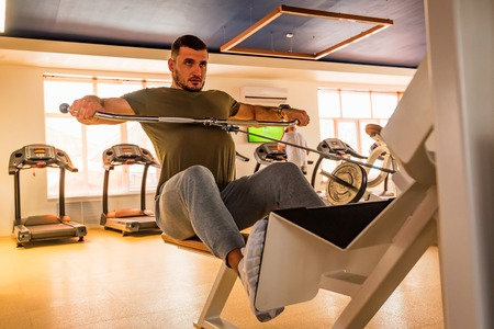 Young muscular man does lower chest exercises with machine in modern gym