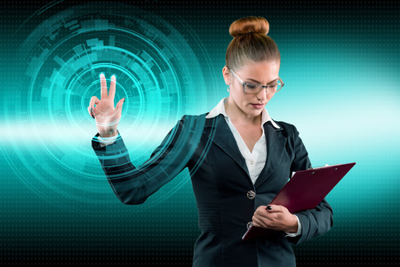 Young business lady works with virtual graphic interface in futuristic office