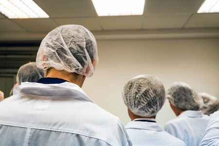 Food factory workers in uniform back view