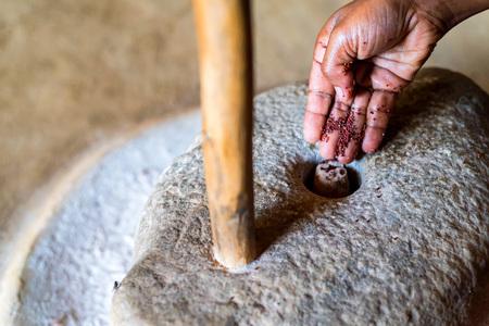 Hands work with millstone to grind sorhum in Sri lankan house