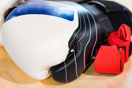 Black, blue and white boxing glove on light background
