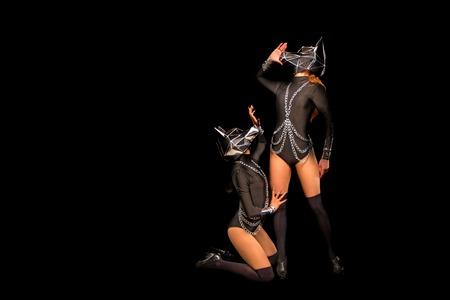 Zwei Go-Go-Varieté-Show-Tänzer in Wolfsmasken auf Schwarz