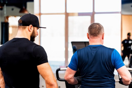 Back view personal trainer coaching male sportsman on machine in modern gym