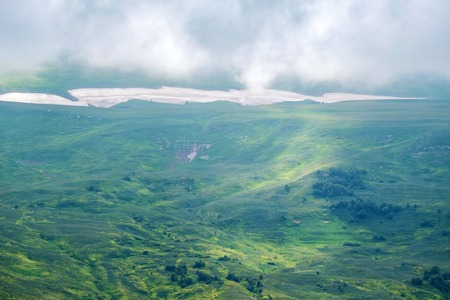 Beautiful mysterious landscape with green valley and cloudy sky