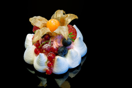 Close up of meringue cake with berries isolated on darkbackground.