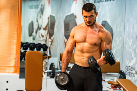 Male athlete doing biceps exercise with dumbbells