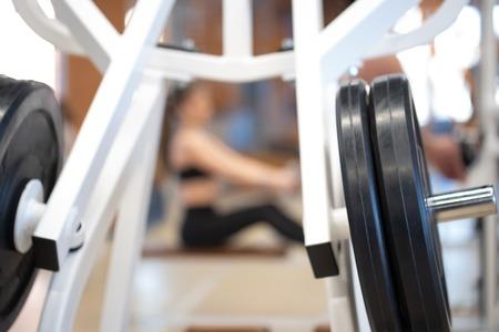 Placas de peso con mancuernas y barras de fitness de la máquina de ejercicio en el gimnasio Foto de archivo