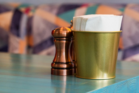 Salt in brown chrome casters and bucket with napkins in restaurant
