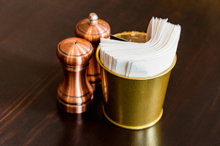 Salt in brown chrome casters and bucket with napkins in restaurant Stockfoto