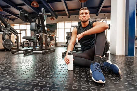 Male athlete sits with fitness drink in modern gym