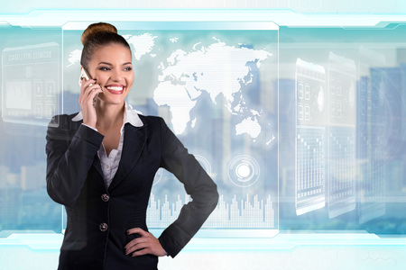 Young business lady speaks on the phone and works in futuristic office