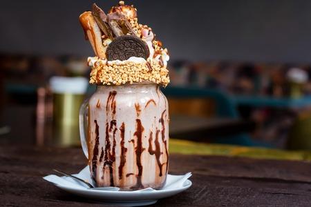 Tasty milkshake with waffles, cream, biscuits and nuts served in jar