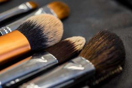 Set of makeup brushes lying on darn surface close