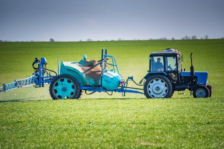 Tractor azul con dispositivo de pulverización en campo verde