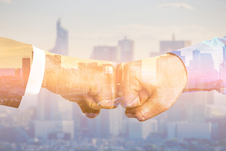 Partners fistbump with multiple exposure. Global business concept