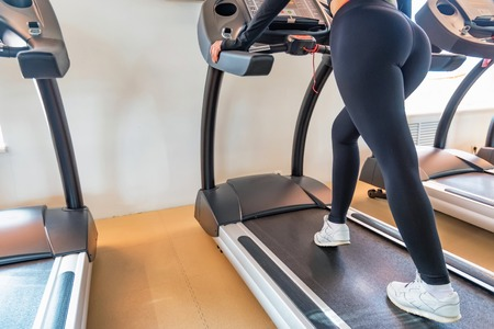 Close up young fit woman on modern treadmill in gym. Lower part view
