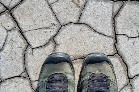 Top view hiking boots on dry muddy soil surface for  texture Imagens
