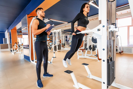 Personal trainer coaching female bodybuilder making dip exercise on machine