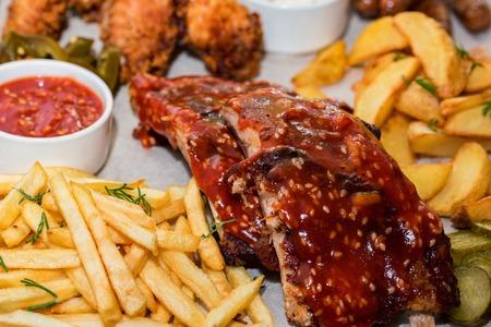 Plat de viandes mixtes. Côtes levées grillées, ailes de poulet et saucisses avec frites Banque d'images